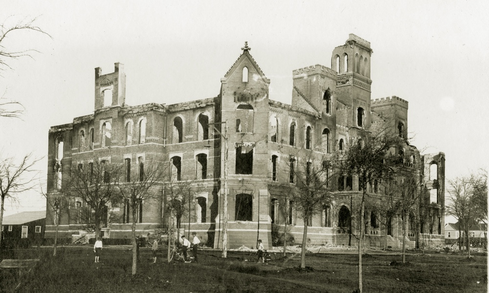 The charred remains of a four-story stone building, TCU's Waco campus main building after a fire