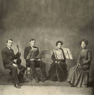 Four student musicians from 1911 pose for a photo with instruments