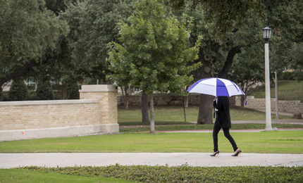 Pedestrian with umbrella walks across campus