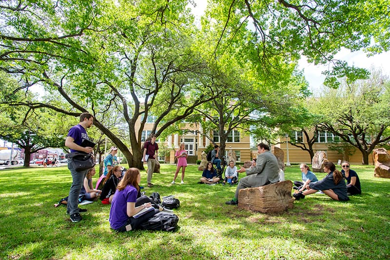 A professor sitting outside on a large boulder teaching students surrounded by tall trees with bright green leaves