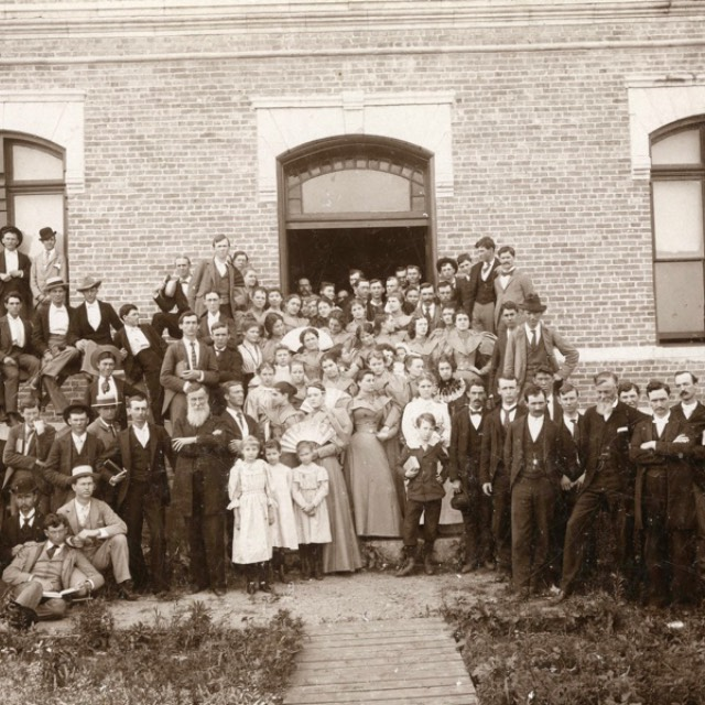 A group of students and faculty gathers for a photo in front of one of the buildings of AddRan Christian University in 1895