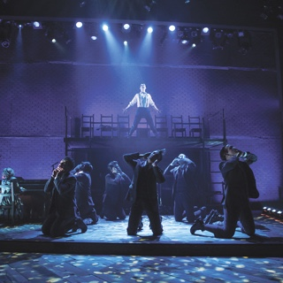 An a scene from TCU's presentation of the musical Spring Awakening, an ensemble of actors in period costume kneel while a male soloist sings under a blue spotlight on an elevated platform.