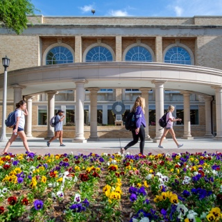 TCU students walk by a flowerbed of multi-color pansies on a sunny day near the library