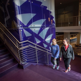 Two girls walk up a staircase in the multi purpose building at TCU's Worth Hills