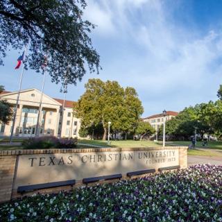 A brick sign bearing the name Texas Christian University sits behind a flowerbed of purple pansies
