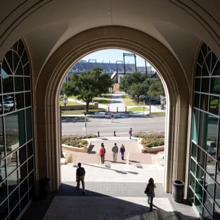 TCU students walk through the University Union arch with the football stadium in the background