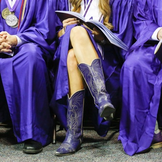 A TCU graduate wears purple cowboy boots with her commencement gown