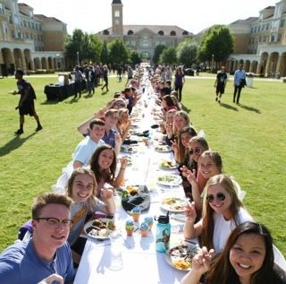 Students dine together at table that stretches the length of the TCU campus commons