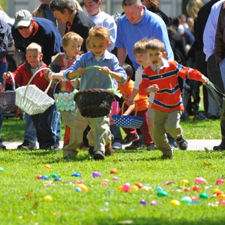 A group of young children holding Easter baskets run across a lawn covered with plastic eggs while their parents cheer behind them.
