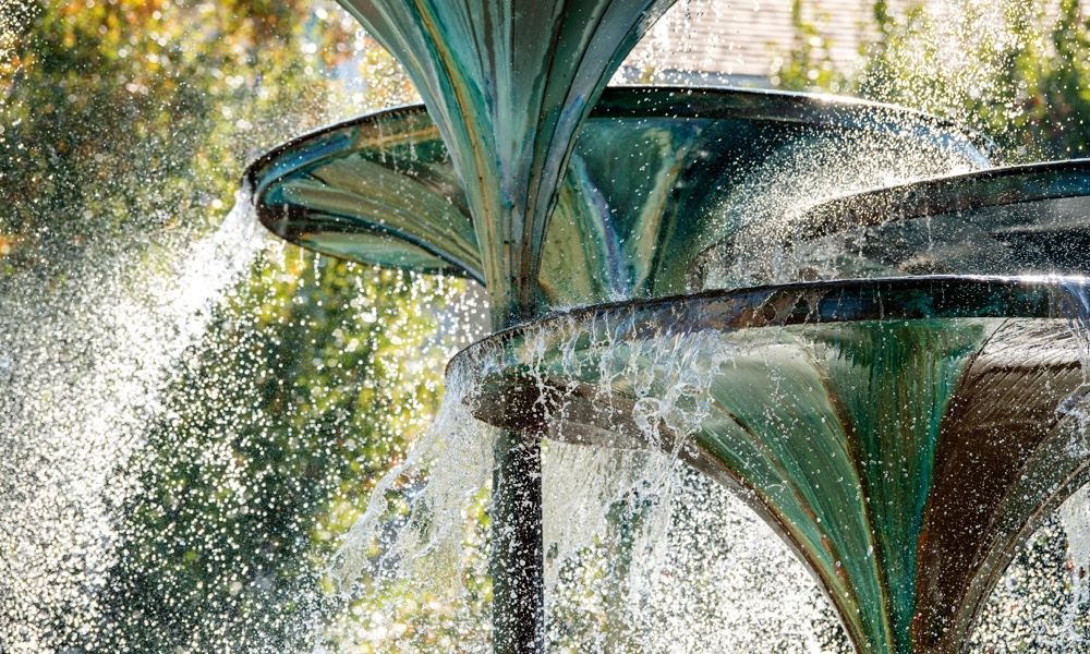 Close up view of water cascading from the trumpet-shaped forms of TCU landmark Frog Fountain