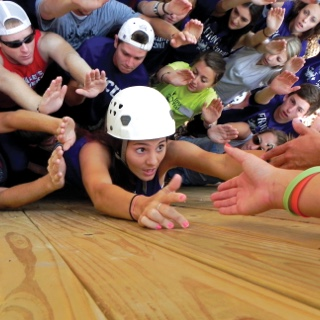 A young women wearing a protective rock-climbing helmet reaches up to the waiting hands of teammates as she scales a wooden outdoor obstacle course wall, surrounded by friends.