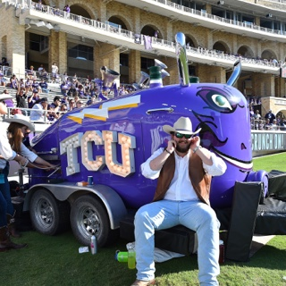 "A large purple train horn mounted on a trailer with the ""TCU"" logo lit up in bright white lights"