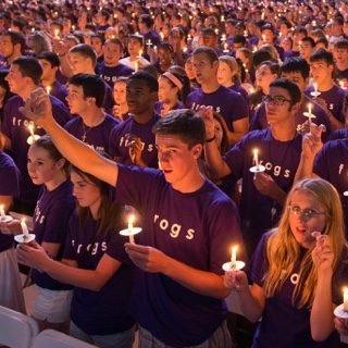 A large group of students — all with purple Go Frogs shirts and each with a lit candle — gather during the Chancellor's Assembly