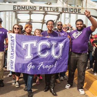 A group TCU students walks across the Edmund Pettus Bridge in Selma, Alabama. They hold a TCU flag and several students make the wo-fingered Go Frogs hand gesture.
