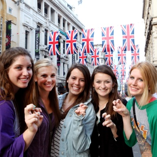 A group of five female TCU students studying abroad make the two-fingered Go Frogs hand sign while standing together on a street in London.