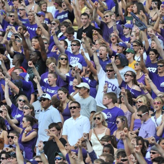 "Dozens of cheering TCU fans raise their arm in a two-fingered ""Go Frogs"" hand sign at a crowded football game."