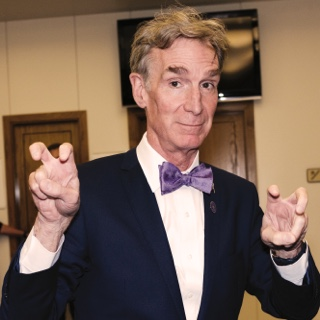 Visiting author and television host Bill Nye holds up both hands in the two-fingered Go Frogs hand gesture.