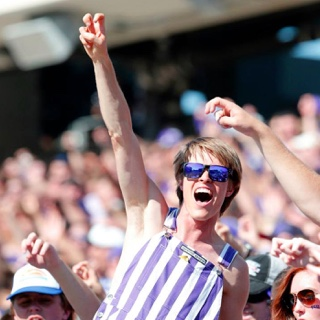 "A happy, cheering student in striped overall and purple sunglasses makes the two-fingered ""Go Frogs"" hand sign at a crowded football game."