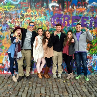 Seven TCU students studying abroad stand in front of a brightly spray-painted graffitti wall on a cobblestone street in Prague.