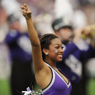 "A smiling TCU Showgirl makes the two-fingered ""Go Frogs"" hand sign at a crowded football game."