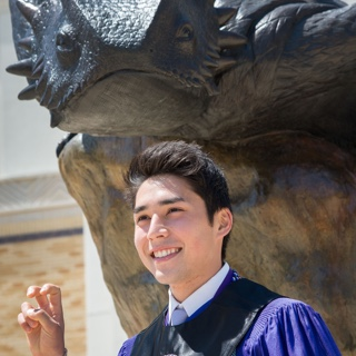 "A male TCU student in Honors regalia makes the two-fingered ""Go Frogs"" hand sign in front of a bronze statue"