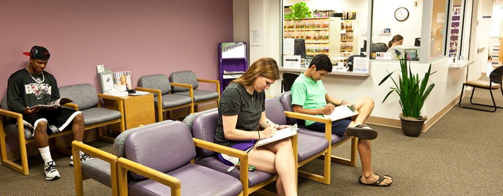 Several students sit in the health center waiting room
