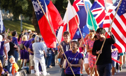 "A group of laughing students carry flags of different nations in a TCU Homecoming parade, led by a girl wearing a shirt that says ""Frogs"""