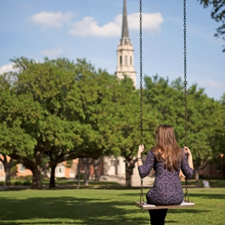 Back of female TCU student sitting in a metal swing with a cluster of trees and the TCU chapel in the background.
