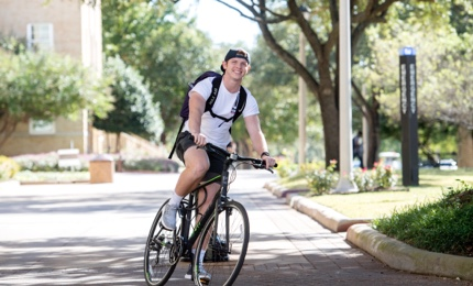 Male student riding a bike on campus
