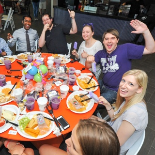 A group of TCU students raise their celebratory purple margaritas at a festive round table