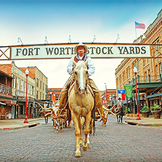 "A cowboy in customary western attire rides a brown and white horse underneath a ""Fort Worth Stock Yards"" sign that spans across a street lined with old western buildings"