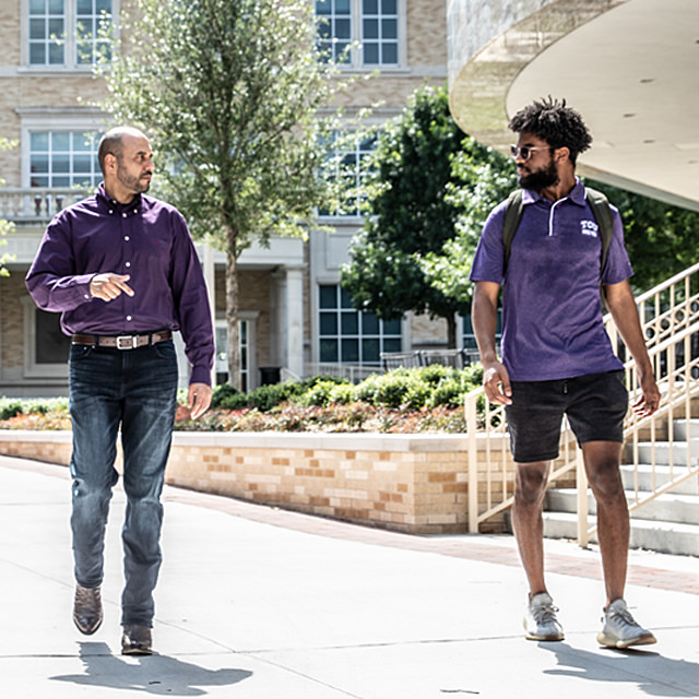 TCU professors chatting with a student as they walk across campus