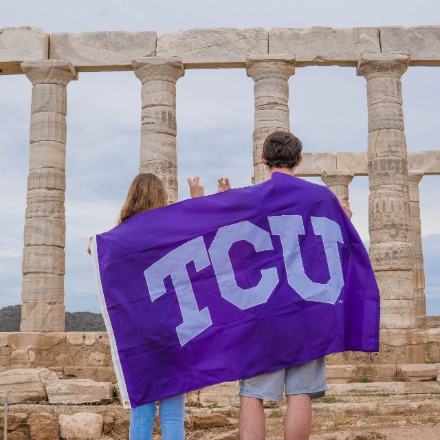 Two students, backs toward us, drape a TCU flag across their shoulders as they look at the pillars of a classical monument