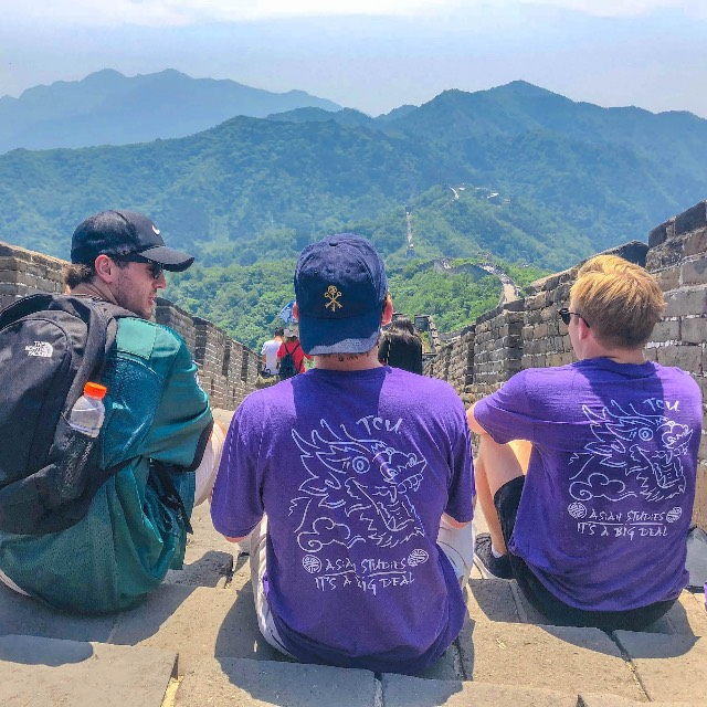 Three students sit atop the Great Wall of China