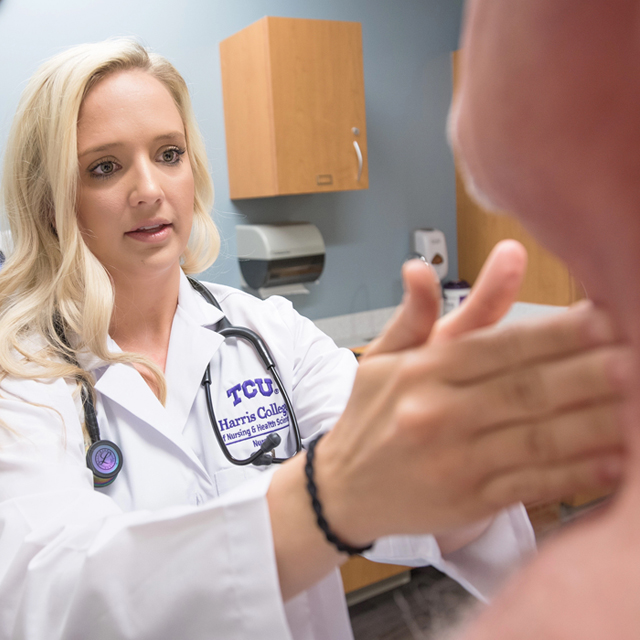 A clinical nurse leader student checks talks to a faculty member