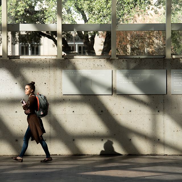 A student carrying a backpack walks through the Moudy Building as the structure's architectural features cast shadows dramatically on a concrete wall