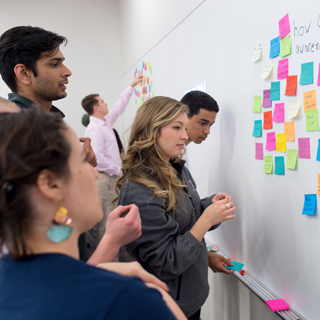 Students at a whiteboard arranging brightly colored sticky notes as part of a design thinking project
