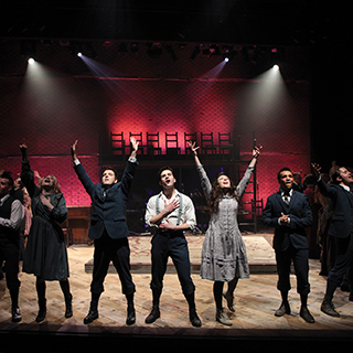 Student actors in a theatrical production of Spring Awakening sing together on stage