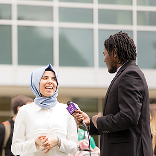 A student reporter holds a microphone up to a student wearing a hijab while a student with a video camera records the interview