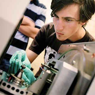 A male student wearing green protective gloves works on a piece of electronics