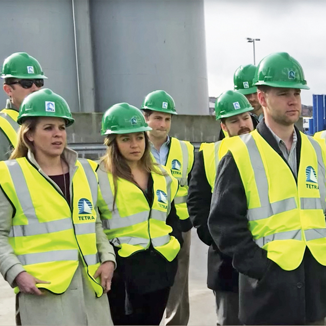 Group of Energy MBA students on site wearing hard hats and safety vests