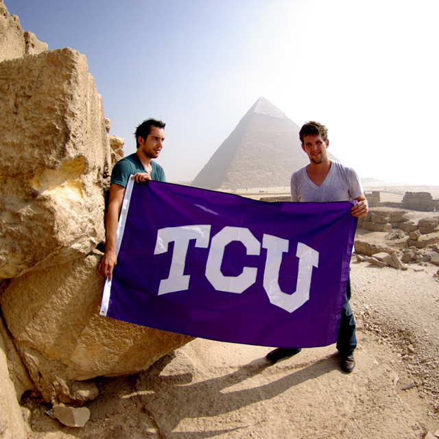 Two male students near pyramid with TCU flag