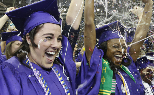 TCU graduates in caps and gowns set off handheld confetti cannons spewing multi-colored confetti into the air