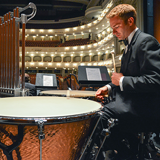 A male TCU music student in a tuxedo rehearses percussion at Fort Worth's Bass Performance Hall