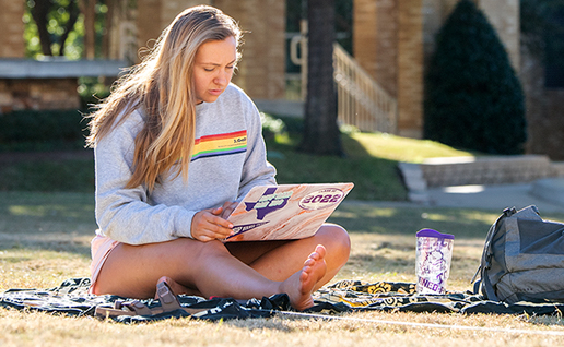A barefoot girl sits on a blanket on the lawn of the TCU campus common, looking at her laptop.