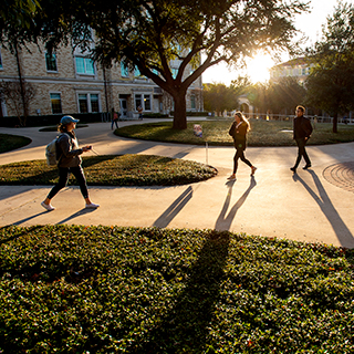 TCU students wearing jackets walk on campus, casting long shadows on a sunny day