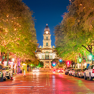 A northerly view at night looking up a downtown street lined with trees adorned with sparkling white lights to the county courthouse