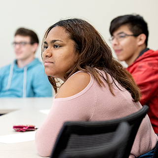 Three TCU students of different ethnicities listen together in a classroom. A young woman in a pink sweater is in the foreground.