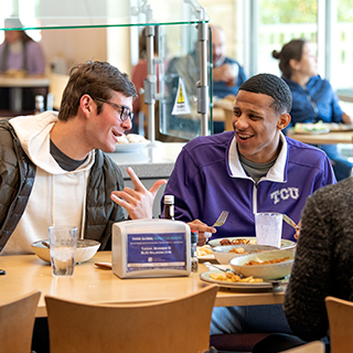 Two male TCU students share a laugh over lunch at the campus main dining hall