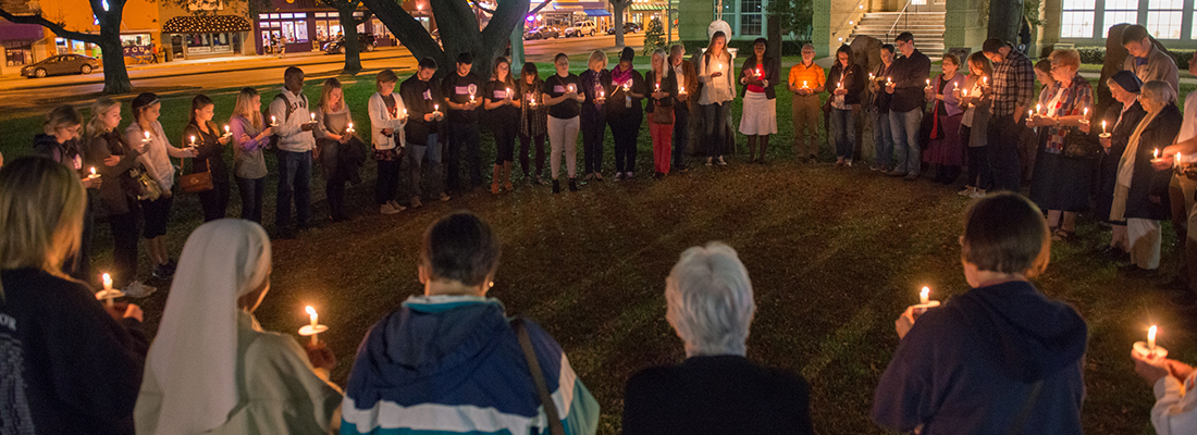 A circle of people holding candles gather for a nighttime prayer vigil on the lawn of the TCU campus.